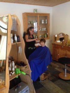 Ich, Susanne Lins beim Schneiden der Haare einer Kundin, im Naturfriseur Grüne Schere in Jean